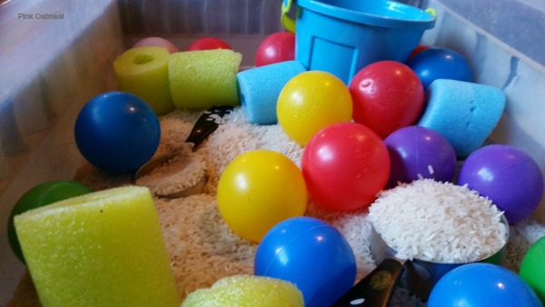 Sensory Bin With Balls, Bucket, and Noodles - Pink Oatmeal