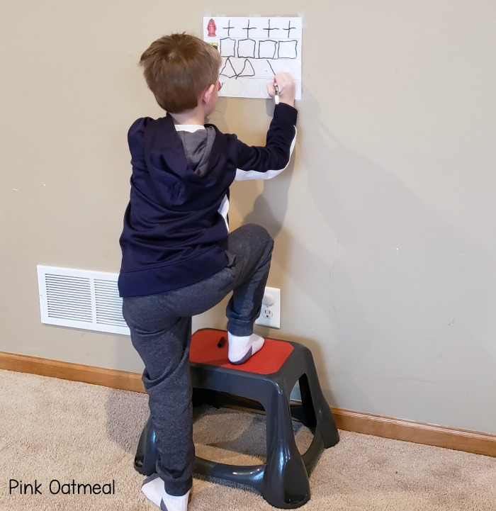 Balance exercises for kids - standing with one foot on the stool and one foot on the ground.